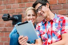 Hipster tourists planning Berlin vacation with pad computer. Hipster tourists, women and man, planning their Berlin vacation with a pad computer sitting in front Stock Image