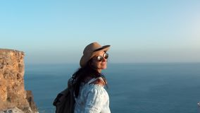 Hipster travel female having fun smiling walking on top of mountain over sea at sunset. Steadicam establish shot. Attractive young woman in hat and sunglasses stock footage