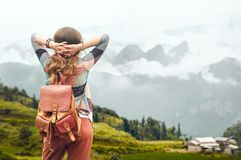 Hipster traveler with backpack enjoying view at mountains in fog Royalty Free Stock Photography