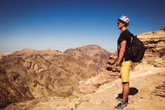 Hipster traveler contemplate impressive mountains landscape. Man with backpack and hat standing alone on top mountain enjoy freedo. M. Wanderlust travel concept stock image