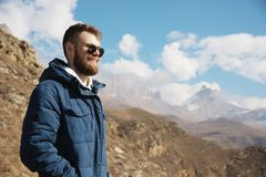 Hipster traveler in a down jacket and sunglasses stands on a mountain slope against the backdrop of epic rocks and. Smiles. The concept of finding happiness in Stock Photos