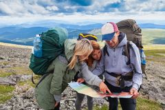 Hipster traveler on top of mountains. A team of travelers from two women and men with backpacks orient themselves to the terrain, study maps and navigate the stock photography