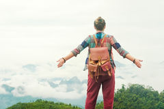 Hipster traveller with backpack and raised hands enjoying view a Royalty Free Stock Photo