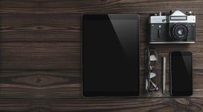 Hipster uitstekende houten Desktop met mobiele telefoon, oogglazen, pen, camera en tablet stock fotografie