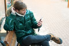 Hipster use smartphone on winter day. Man handsome hold smartphone. Guy sit bench interact smartphone. Man unshaven wear. Warm jacket and hold smartphone snowy royalty free stock photography