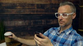 Hipster using a phone in a cafe. Dolly shot of hipster using a phone in a cafe stock video footage