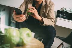 Hipster using smart phone and digital tablet computer and holdin. G credit card payments online business,sitting on sofa in living room,work at home concept Stock Image