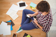 Hipster using smartphone while holding black coffee in office Royalty Free Stock Image