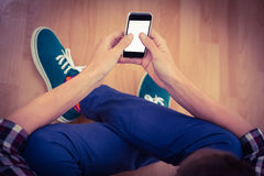 Hipster using smartphone while sitting on hardwood floor Stock Photo