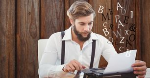 Hipster using typewriter against wall Stock Photos