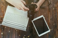 Hipster vintage wooden desktop top view, male hands holding photocamera watching photos. stock image