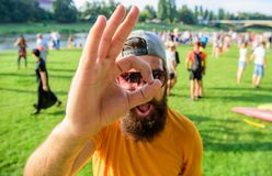 Hipster visiting fest festival. Man cheerful face looks through ok gesture. Man bearded in front of crowd riverside. Background. Book ticket summer festival in stock images