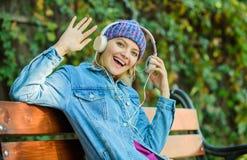 hipster vrouw in hoofdtelefoons het luisteren muziek in park moderne technologie in plaats van lezing Ontspan in park Uitstekende royalty-vrije stock afbeelding