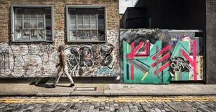 Hipster walking along grafitti-covered street Royalty Free Stock Photo