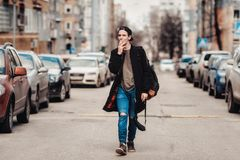 Hipster walking around the city on the street among cars stock photo