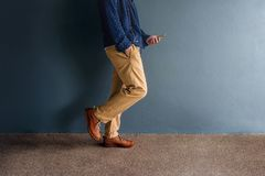 Hipster Walking and Reading Smart Phone at Dark wall, Side View, Royalty Free Stock Images
