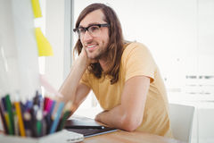 Hipster wearing eye glasses working at computer desk Stock Photos
