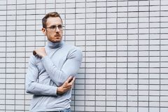 Hipster wearing glasses, standing near the wall made of small tiles. Man, hipster, wearing glasses, wearing grey turtleneck standing near the wall made of small royalty free stock image