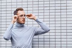 Hipster wearing glasses, standing near the wall made of small tiles. Man, hipster, wearing glasses, wearing grey turtleneck standing near the wall made of small royalty free stock photos