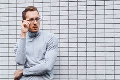Hipster wearing glasses, standing near the wall made of small tiles. Man, hipster, wearing glasses, wearing grey turtleneck standing near the wall made of small royalty free stock images