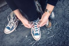 Hipster wearing sneakers, teenager tieing laces at sport shoes. Urban lifestyle with footwear and modern clothing. Stock Images