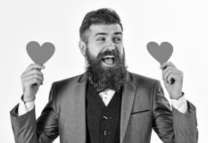 Hipster wears formal suit. Happy man with long beard and smiling face. Bearded man smiles and holds red hearts. Dating stock photo