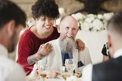 Lucky Father Of The Bride!. Hipster wedding guest has kissed the father of the bride with lipstick on. They are both laughing with other guests at the lipstick royalty free stock photo