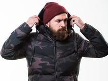Hipster winter fashion. Guy wear hat and black winter jacket. Comfortable winter outfit. Winter stylish menswear. Man. Bearded stand warm camouflage pattern royalty free stock image