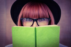 Hipster woman behind a green book Stock Photo