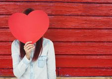 Hipster woman  with the face covered with a heart.  red wood background Stock Image