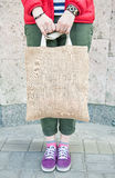 Hipster woman holding empty canvas bag outdoor. Template mock up stock image