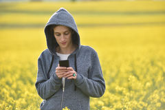 Hipster woman in hoodie using her smart phone in outdoors Stock Photo