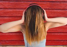 Hipster woman listening music with red wood background. Digital composite of hipster woman listening music with red wood background Royalty Free Stock Photography