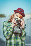 Hipster woman making picture with retro camera, focus on camera Stock Photography