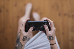Hipster Woman Playing Playstation 4. Gothenburg, Sweden - September 17, 2016: A close up shot from above of a tattooed young woman's hands holding a black video Stock Photography