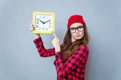Hipster woman pointing finger on wall clock stock photography