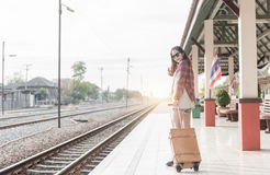 Hipster woman pull brown leather vintage bag at railway station. Stock Photos