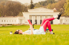 Hipster woman reading a book outdoors and lying on back. In nature in the city park Royalty Free Stock Photo