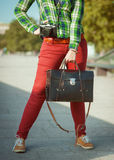 Hipster woman in red pants and green shirt with old suitcase Stock Images