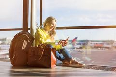 Woman sitting in airport and using her smartphone Royalty Free Stock Image