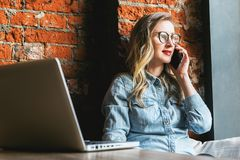Hipster woman sitting in cafe leaning on brick wall and talking on mobile phone.Girl calls taxi, makes order by phone. royalty free stock image