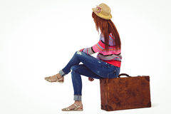 Hipster woman sitting on her suitcase Royalty Free Stock Image