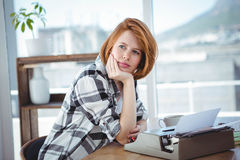 Hipster woman sitting at her typewriter, thinking Royalty Free Stock Photography