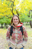 Hipster woman is smiling while standing in the autumn park. Stock Image