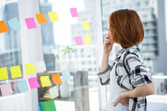 Hipster woman staring at notes on thee wall an thinking Royalty Free Stock Photos