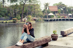 Hipster woman taking photos with retro film camera in outdoor ci Stock Photos