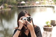 Hipster woman taking photos with retro film camera in outdoor ci Stock Images