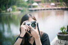 Hipster woman taking photos with retro film camera in outdoor ci Royalty Free Stock Photo