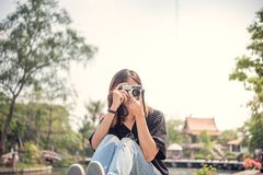 Hipster woman taking photos with retro film camera in outdoor ci Stock Photo