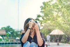 Hipster woman taking photos with retro film camera in outdoor ci Royalty Free Stock Photography